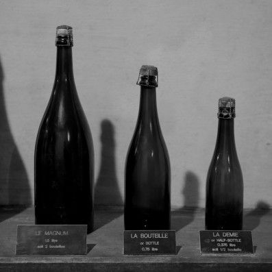 Different Champagne bottle sizes displayed in Maison Taittingers