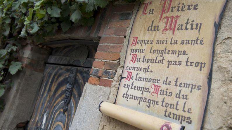 """Una puerta antigua en la población de Hautvillers con el mensaje: """"Que me den salud durante mucho tiempo. Trabajo no muy a menudo. Amor de vez en cuando. Pero champán siempre."""""""